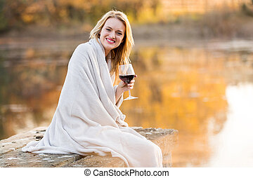 smiling woman drinking red wine at sunset