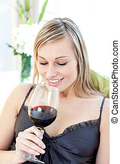 Smiling woman drinking red wine