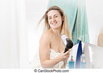 Smiling woman drying long blonde hair after having shower