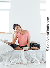 Smiling woman eating cereals with milk on bed in bedroom