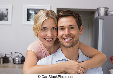 Portrait of a smiling young woman embracing man from behind in kitchen at home