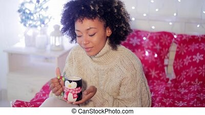 Smiling woman enjoying a cup of Christmas coffee