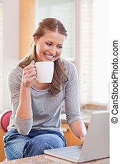 Smiling woman enjoying coffee while typing on her laptop