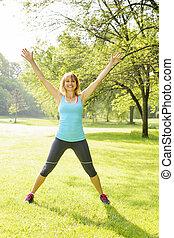 Smiling woman exercising outside