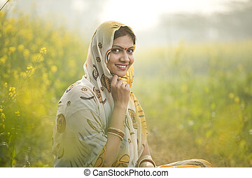 Smiling woman farmer in rapeseed agricultural field