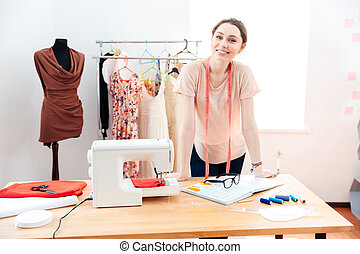 Smiling woman fashion designer standing and working in studio