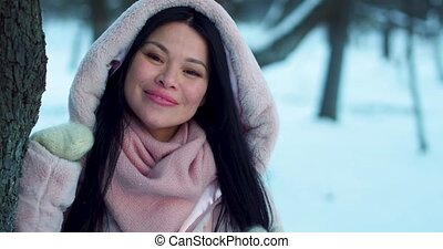 Smiling woman from Asia in snowy garden. - Smiling female...