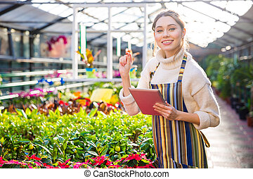 Smiling woman gardener using tablet in greenhouse