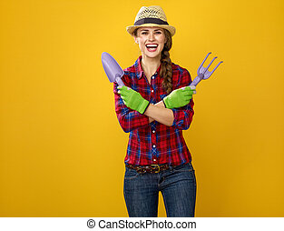 smiling woman grower on yellow background with gardening...