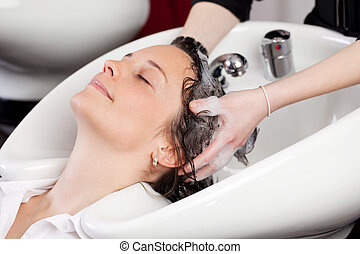 Smiling woman having a hair shampoo - Smiling attractive...