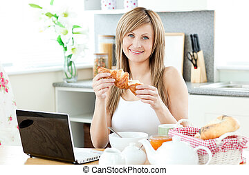 Smiling woman having breakfast in front of the laptop in the kitchen at home