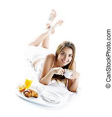 Smiling woman having breakfast