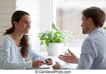 Smiling happy woman having pleasant conversation with male colleague during break, discussing new interesting idea, talking about project at workplace, having fun together, laughing at joke
