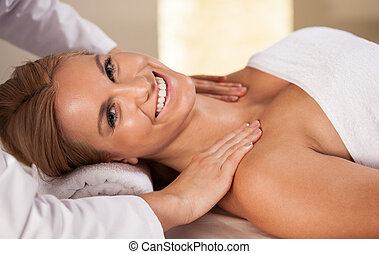 Smiling woman having shoulder massage