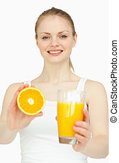 Smiling woman holding a glass while presenting an orange