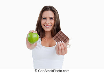 Smiling woman holding a green apple and a piece of chocolate