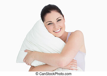Smiling woman holding a pillow in her arms against white background