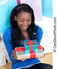 Smiling woman holding a present sitting on the floor