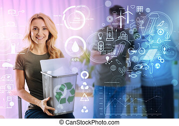 Smiling woman holding a rubbish bin and showing a recycling symbol