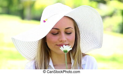 Smiling woman holding a white flower