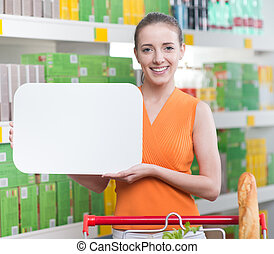 Smiling woman holding a white sign at supermarket