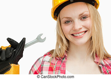 Smiling woman holding a wrench