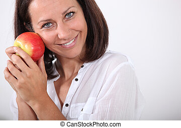 Smiling woman holding an apple to her face