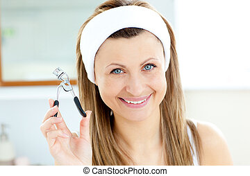 Smiling woman holding an eylash curler looking at the camera
