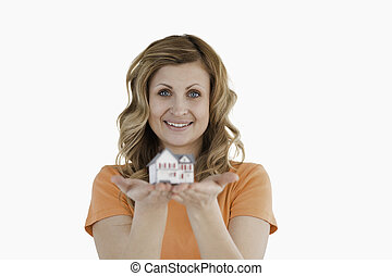 Smiling woman holding an house model