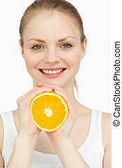 Smiling woman holding an orange in her hands against white...