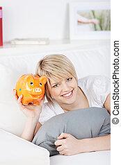 Smiling woman holding an orange piggy bank