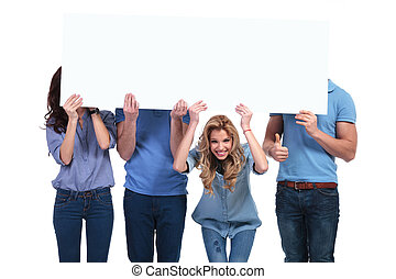 smiling woman holding banner with her friends hiding -...