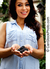 Smiling woman holding blackberries