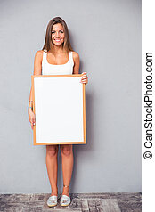 Smiling woman holding blank board - Full length portrait of ...