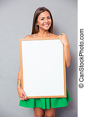 Smiling woman holding blank board - Smiling young woman ...
