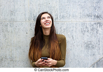 Smiling woman holding cellphone and looking up