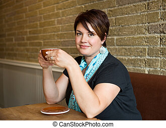 Smiling Woman Holding Coffee Cup In Cafeteria