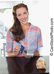 Smiling woman holding credit card at coffee shop counter