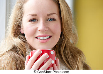 Smiling woman holding cup of tea