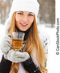 Smiling woman holding cup of tea in her hands