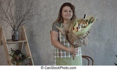 Smiling woman holding edible bouquet arrangement - Cheerful...