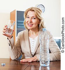 smiling   woman holding glass filled with water