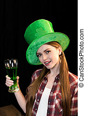 woman holding glass of beer in hand on St.Patrick's day