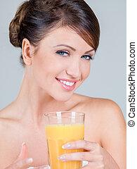 Smiling Woman Holding Glass of Orange Juice
