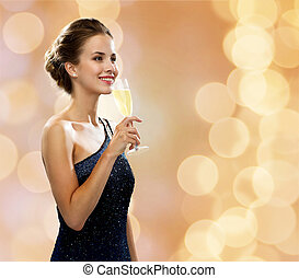 smiling woman holding glass of sparkling wine - party,...
