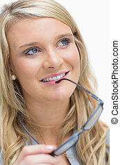 Smiling woman holding glasses at her lips