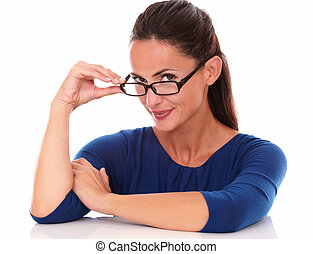 Smiling woman holding glasses while looking at you