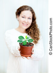 Smiling woman holding green plant