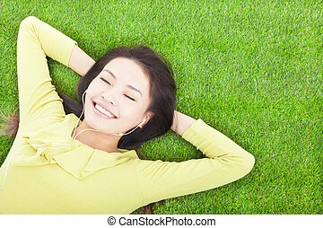 smiling woman holding head and lying on a meadow