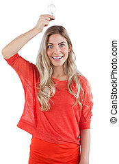 Smiling woman holding light bulb